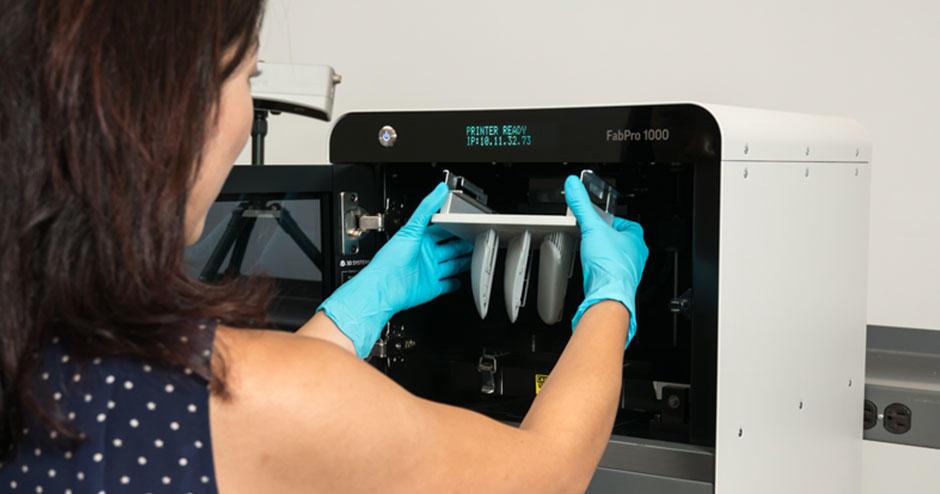 Une femme chargeant des matériaux dans l'imprimante FabPro 3D