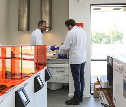 personne dans un laboratoire dentaire entourée de matériel de laboratoire et d'imprimantes3D